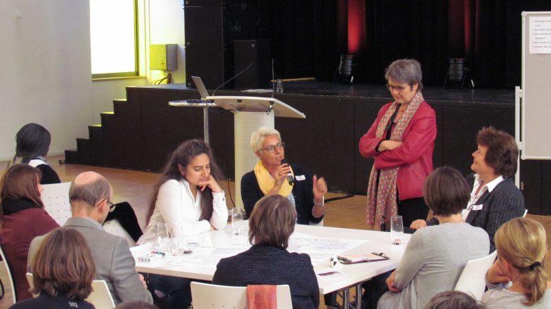 Eine Menschengruppe sitzt an einem Tisch. Eine Frau am Tisch spricht in in Mikrofon. Eine Frau steht neben dem Tich und hört zu.